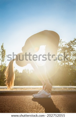 An Attractive Female Runner Stretching Before Workout #202752055