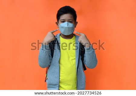 Indonesian boys wearing medical masks get ready to go to school