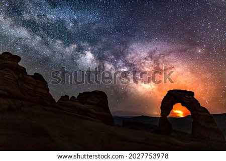 The Pack Creek Fire in the La Sal Mountains lights up the night sky in the distance, with the Milky Way over Delicate Arch in Arches National Park, Utah. Royalty-Free Stock Photo #2027753978