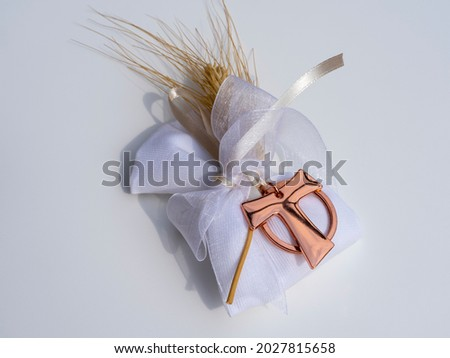 Gifts or favors for the first or holy communion. Isolated small bag of white fabric with ear of wheat and burnished metal Tau Christian cross. Religious symbol Royalty-Free Stock Photo #2027815658