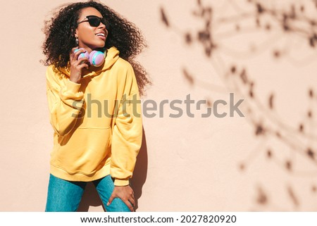 Beautiful black woman with afro curls hairstyle.Smiling model in yellow hoodie.Sexy carefree female enjoying listening music in wireless headphones.Posing on street background near wall in sunglasses