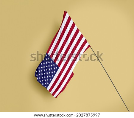 United States flag fluttering on a subtle yellow background Royalty-Free Stock Photo #2027875997
