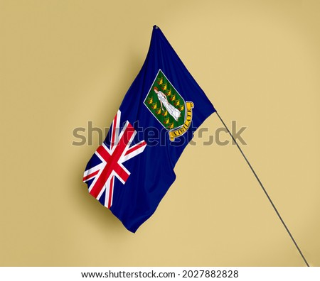 British Virgin Island flag fluttering on a subtle yellow background Royalty-Free Stock Photo #2027882828