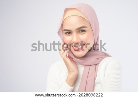 A portrait of young smiling muslim woman wearing a pink hijab over white background studio. Royalty-Free Stock Photo #2028098222