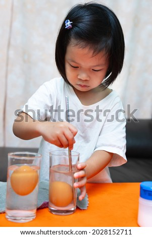 Cute Asian 4-5 years girl is learning with science experiments on buoyancy with the Floating Eggs in plain water and salted water. Children are working with water mixed with salt to dissolve the salt.