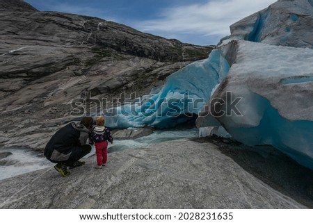 Dad and son take pictures of the glacier.Norway.