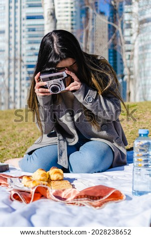 young hispanic latina woman at a picnic in the city taking a picture with a vintage camera of some pastries, argentinian facturas. medialunas. typical argentinian breakfast.