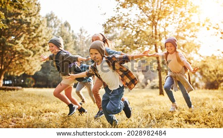 Group of happy joyful school kids with backpacks running with outstretched arms in forest on sunny spring day, excited children scouts boys and girls having fun during camping activity in nature Royalty-Free Stock Photo #2028982484