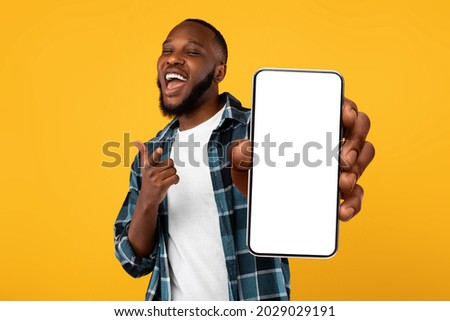 Recommendation. Portrait of excited black guy holding big smartphone with white blank screen in hand, showing close to camera and pointing at device. Gadget with empty free space for mock up, banner Royalty-Free Stock Photo #2029029191