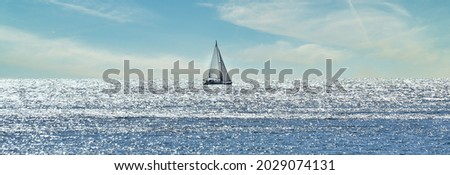 Small sailboat sailing through a silver sea in a sunny day  Royalty-Free Stock Photo #2029074131
