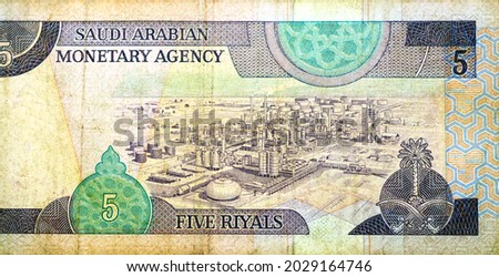 Large fragment of the reverse side of 5 five Saudi riyals banknote currency issued 1983 by Saudi Arabian Monetary Agency with n oil refinery on it, vintage retro old Saudi money, King Fahd Riyals Royalty-Free Stock Photo #2029164746