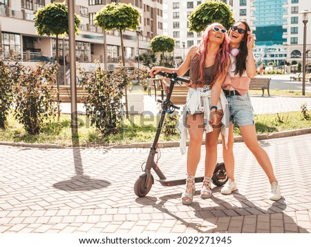 Two young beautiful smiling hipster female in trendy summer clothes.Sexy carefree women posing in the street with pink hair. Positive pure models having fun at sunset. Using electric Kick scooter Royalty-Free Stock Photo #2029271945