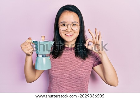 Young chinese girl holding italian coffee maker doing ok sign with fingers, smiling friendly gesturing excellent symbol