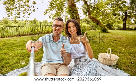leisure and people concept - happy couple having picnic and taking picture with selfie stick and showing thumbs up at summer park