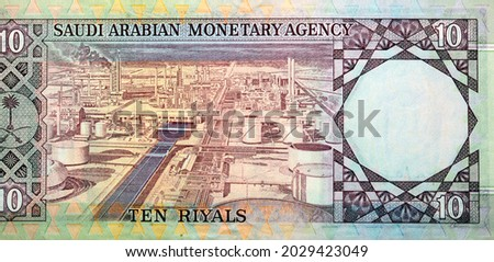 Large fragment of the reverse side of 10 ten Saudi riyals banknote currency issued 1961 to 1977 by Saudi Arabian Monetary Agency with an oil refinery on it, vintage retro old Saudi money, leftover. Royalty-Free Stock Photo #2029423049