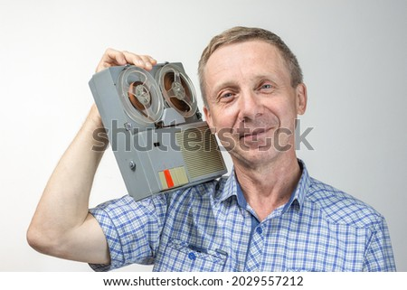 An elderly, blue-eyed, contented man listens to music on an old reel-to-reel tape recorder on a light background Royalty-Free Stock Photo #2029557212