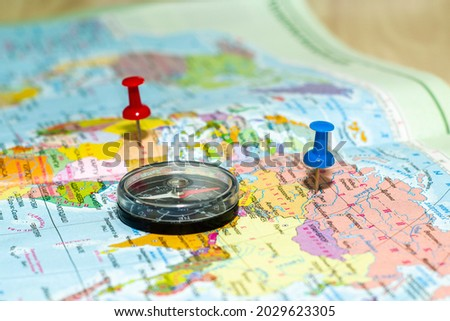 a compass lying on a geographical map buttons mark the place of travel the concept of a tourist. High quality photo Royalty-Free Stock Photo #2029623305