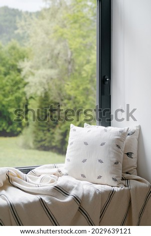 Interior of home room with window, house design. Nobody at sill, modern decor for cozy indoor place. Scandinavian comfortable apartment. Vertical closeup of pillow, blanket at windowsill. Royalty-Free Stock Photo #2029639121