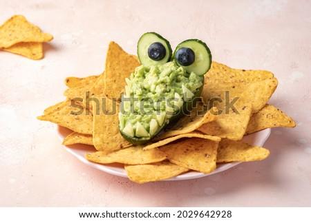 Funny alligator avocado bowl guacamole dip and nachos Royalty-Free Stock Photo #2029642928