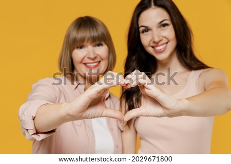 Two young happy daughter mother together couple women wearing casual beige clothes showing close up shape heart with hands heart-shape sign isolated on plain yellow color background studio portrait. Royalty-Free Stock Photo #2029671800