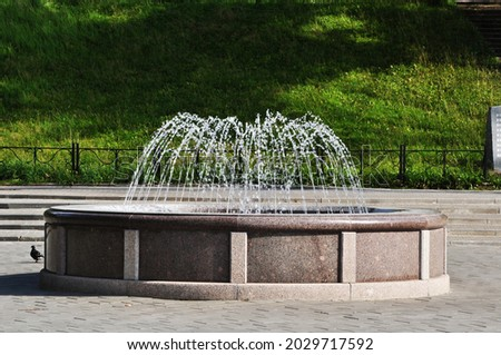 Fountain in the city square. View of the fountain against a background of green grass. Royalty-Free Stock Photo #2029717592