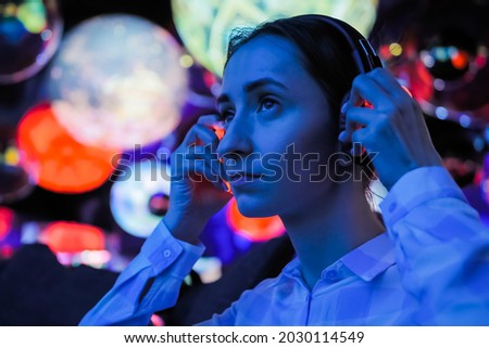 Woman wearing wireless black headphones and looking around in dark room of interactive exhibition or museum with colorful illumination. Futuristic, entertainment, immersive concept Royalty-Free Stock Photo #2030114549