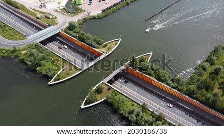 Aerial view of aqueduct or water bridge constructed to convey watercourses across gaps showing recreational boats moving towards the infrastructure and traffic going underneath it Royalty-Free Stock Photo #2030186738