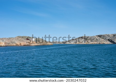 A picture of a beautiful rock island. Ocean and blue sky in the background. Picture from the Weather Islands, on the Swedish West coast