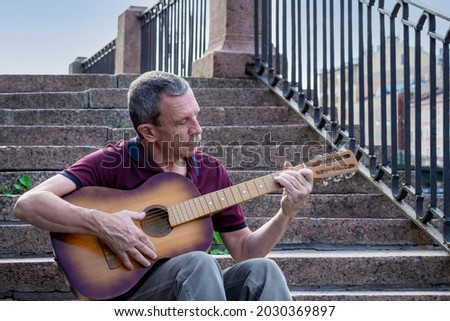 Adult elderly man of retirement age plays old six-string classical acoustic guitar outdoors while sitting on granite staircase on summer evening in city. Hobby, doing what you love. Selective focus. Royalty-Free Stock Photo #2030369897