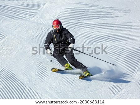 professional skier at speed in a turn. a screensaver with a ski slope with traces after a snowmobile and an athlete in a black jumpsuit and a red helmet. copy space