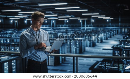 Portrait of IT Specialist Uses Laptop in Data Center. Server Farm Cloud Computing Facility with Male Maintenance Administrator Working. Cyber Security and Network Protection. Royalty-Free Stock Photo #2030685644
