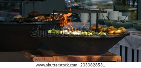 chef cooks broccoli, potatoes and meat at street food festival, barbeque. High quality photo Royalty-Free Stock Photo #2030828531