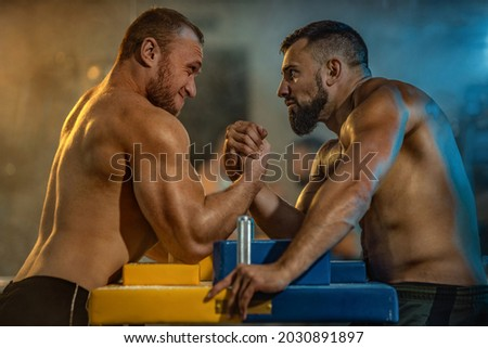 Two strong athletes in the gym compete in arm wrestling. Bodybuilders armwreslers in athletic training room