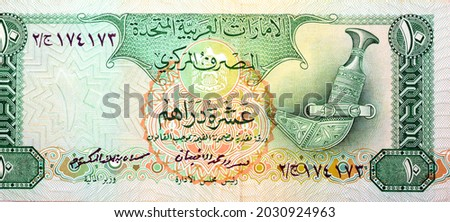 Obverse side of 10 ten Dirhams banknote of the United Arab Emirates, currency of the UAE issued 1982 with a traditional dagger on the right, old Emirates money, vintage retro Royalty-Free Stock Photo #2030924963