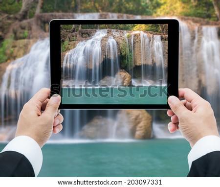 Businessman hands tablet taking pictures Waterfall deep forest  at Erawan waterfall National Park Kanchanaburi of Thailand