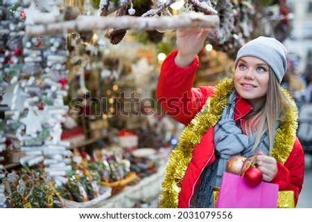 Young smiling woman choosing Xmas decoration on outdoor market Royalty-Free Stock Photo #2031079556