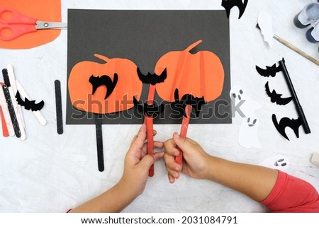 Child making pumpkins for the holiday of halloween. Funny crafts from paper. Halloween decor. Handicraft. The concept for Halloween. DIY. Children's art project, a craft for children.
