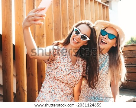 Two young beautiful smiling hipster female in trendy summer clothes.Sexy carefree women posing on the street background in hat. Positive pure models having fun at sunset, hugging. Taking selfie photos