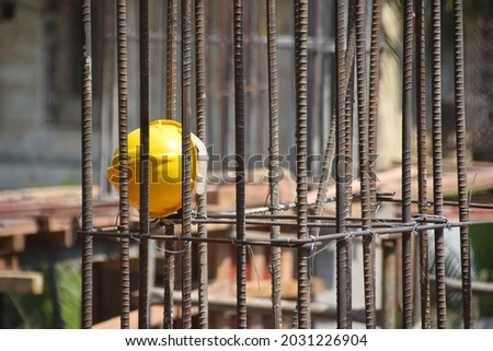 Bright yellow helmet left by the workers at a construction site with shallow depth of field. Thousands of migrant laborers have fled metropolitan cities due to Covid-19, Corona virus. Royalty-Free Stock Photo #2031226904