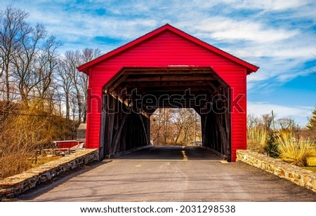 Red wooden covered bridge over the river. Covered bridge road. Red covered bridge view. Covered bridge entrance Royalty-Free Stock Photo #2031298538