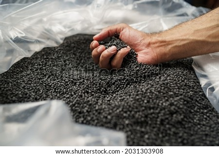 Close up of male hand holding plastic polymer granules Royalty-Free Stock Photo #2031303908
