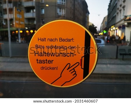 """Sign on exit door of a streetcar in Dresden with the inscription """"Stop as needed: Please press stop request in time!"""" Royalty-Free Stock Photo #2031460607"""