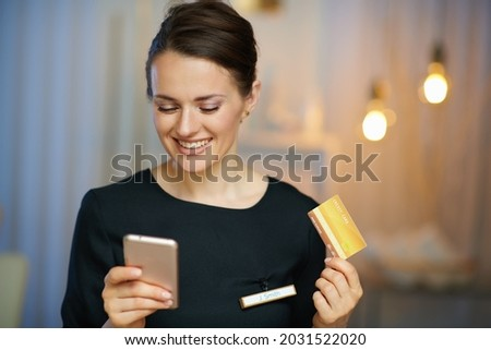 smiling woman worker with smartphone and credit card making online shopping on e-commerce website in modern beauty salon.