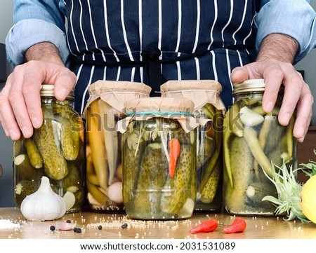 Artisanal. A man is doing pickles jars stock for winter season. Organic homemade cucumber pickles. Man in blue denim shirt and apron is holding his hands on jars lids