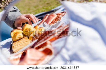 argentinian facturas, typical argentinian pastry dessert, breakfast of croissants at a picnic in a park. reflection in a mirror. artistic picture