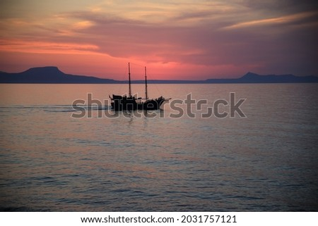 Silhouette of onely boat in the sea with the sunset background. Rethymno, Crete, Greece. High quality photo