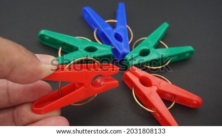 The clothespins are made of plastic with a little additional iron attachment, and there are many color options. Royalty-Free Stock Photo #2031808133