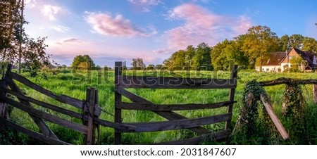 Wooden fence on the farm. Farm fence view. Wooden farm fence. Fence in farm land Royalty-Free Stock Photo #2031847607