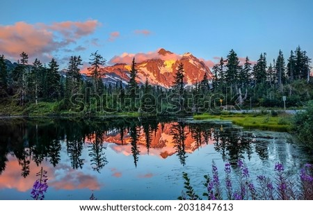 Mountain peak by the lake in the sunset. Mountain lake panorama. Mountain lake view. Sunset mountain lake Royalty-Free Stock Photo #2031847613