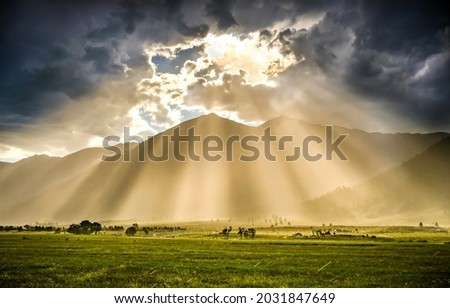 The rays of the sun from behind the clouds illuminate the valley. Sunrays from sky clouds. Cloudy sky sunrays. Beautiful sunrays from cloudy sky Royalty-Free Stock Photo #2031847649